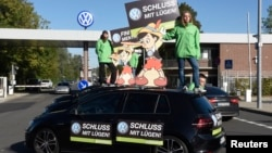 """Greenpeace activists hold banners reading """"No more lies"""" as they stand on top of Volkswagen cars in front of VW's """"Sandkamp"""" gate in Wolfsburg, Germany, Sept. 25, 2015."""