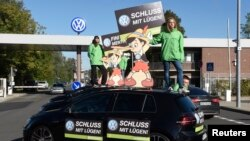 "Greenpeace activists hold banners reading ""No more lies"" as they stand on top of Volkswagen cars in front of VW's ""Sandkamp"" gate in Wolfsburg, Germany, Sept. 25, 2015."