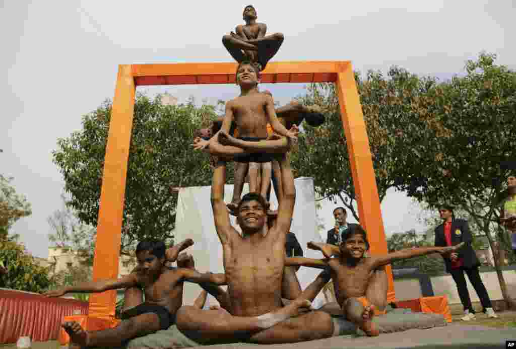 Indian boys perform Mallakhamba, a traditional Indian gymnastic sport on a vertical wooden pole, at a school in Ahmadabad.