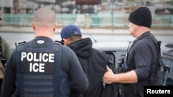 FILE - U.S. Immigration and Customs Enforcement officers detain a suspect as they conduct a targeted enforcement operation, Feb. 7, 2017.