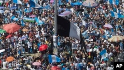 FILE - Protesters raise a black Guatemalan flag in Constitution Plaza as they demand the resignation of Guatemalan President Jimmy Morales in Guatemala City, Sept. 20, 2017.