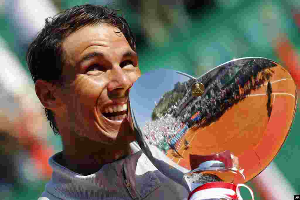 Spain's Rafael Nadal holds the trophy as he celebrates winning the men's singles final match of the Monte Carlo Tennis Masters tournament against Japan's Kei Nishikori in two sets, 6-3, 6-2, in Monaco.
