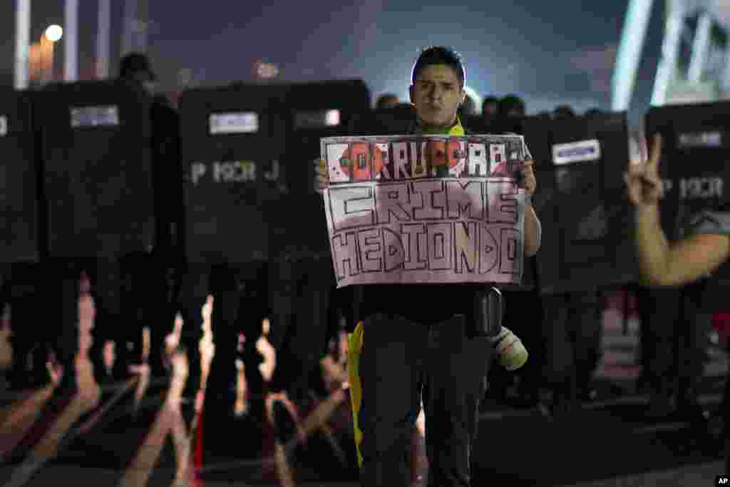 "A man holds a sign that reads in Portuguese: ""Corruption: Heinous crime,"" at an anti-government protest in Rio de Janeiro, Brazil, June 21, 2013."