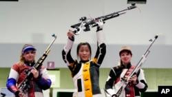 中国选手杨倩在女子10米气步枪的比赛中摘取本届奥运会首枚金牌后将步枪举起(2021年7月24日)