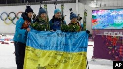 Ukraine's relay team, from left: Vita Semerenko, Juliya Dzhyma, Olena Pidhrushna and Valj Semerenko, with Ukrainian flag with writings on it after winning the gold in the women's biathlon 4x6k relay at the 2014 Winter Olympics, Feb. 21, 2014, in Krasnaya Polyana.