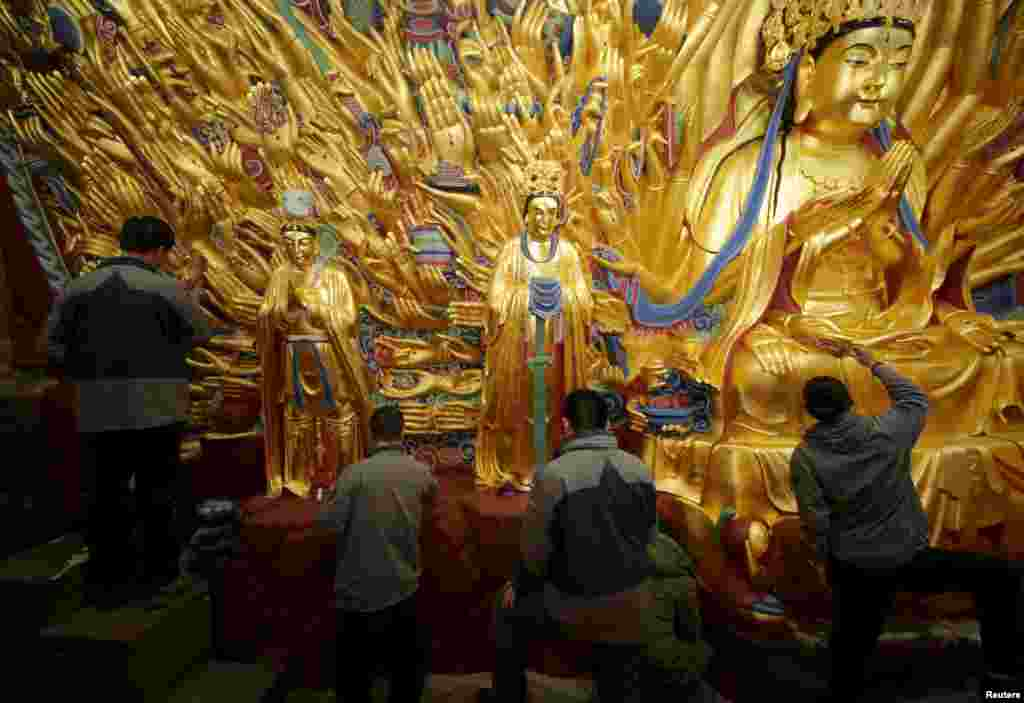 Workers paint as they restore the gold foil on the thousand-hands Bodhisattva in Chongqing Municipality, China, March 25, 2015.