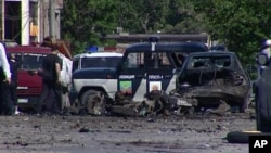This image taken from AP video shows the scene of a blast with wreckage of a police car and debris littered over the ground in Makhachkala in the southern Russian region of Dagestan, May 25, 2013.