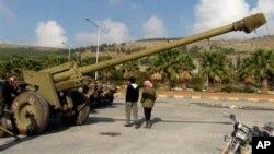 Сирийские повстанцы осматривают орудие, захваченное у сирийской правительственной армии под Алеппо. 25 ноября 2012 г.