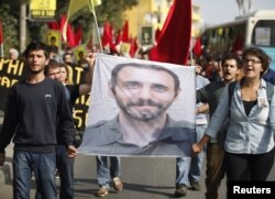 FILE - Students carry a portrait of Nejat Agirnasli, a People's Protection Unit (YPG) fighter who was killed during clashes with Islamic State militants in Kobani, during ceremony held in his memory at Bosphorus University in Istanbul, Oct. 17, 2014.