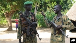 FILE - Two opposition soldiers talk together outside their base in the opposition-held town of Nyal in Unity state, in South Sudan, Aug. 15, 2018.