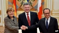 烏克蘭總統波羅申科在2月5日在基輔和到訪的法國總統奧朗的以及德國總理默克爾握手。