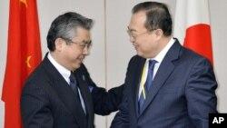 2015年3月19日在东京会晤前日本副外交部长杉山晉辅(左)和中国外交部部长助理刘建超握手