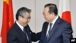 Japan's Deputy Minister of Foreign Affairs Shinsuke Sugiyama, left, and China's Assistant Foreign Minister Liu Jianchao shake hands before their meeting in Tokyo Thursday, March 19, 2015.