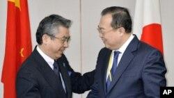 Wakil Menteri Luar Negeri Jepang Shinsuke Sugiyama (kiri) bersama Asisten Menteri Luar Negeri China Liu Jianchao dalam pertemuan di Tokyo (19/3). (AP/Kyodo News)