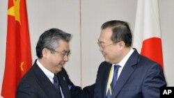Thứ trưởng Ngoại giao Nhật Bản Shinsuke Sugiyama (trái) và Trợ lý Ngoại trưởng Trung Quốc Lưu Kiến Sinh bắt tay trước khi tiến hành cuộc đàm phán tại Tokyo, ngày 19/3/2015.
