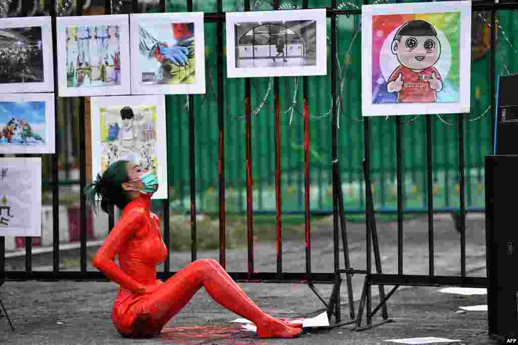 A protester is covered in red paint during a demonstration against the government of Thailand's Prime Minister Prayut Chan-O-Cha and in support of the release of political prisoners outside Bangkok Remand Prison in Bangkok.