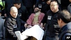 마크 리퍼트 주한 미국대사를 흉기로 습격한 혐의로 체포된 한국인 김기종 씨가 지난해 3월 법원에 출두하기 위해 휠체어에 탄 채 경찰서를 나서고 있다.