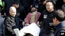Kim Ki-jong, the suspect of slashing U.S. Ambassador Mark Lippert, in a wheelchair is carried by police officers as he leaves a police station for Seoul Central District Court in Seoul, South Korea, Friday, March 6, 2015.