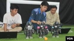 Mahasiswa ITS Surabaya mendemonstrasikan robot pemain sepak bola buatan tim robot ITS. (Foto: VOA/Petrus Riski).