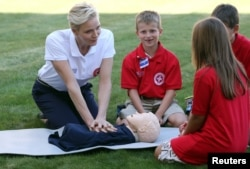 Monaco's Princess Charlene, goodwill ambassador for the International Federation of Red Crosses and Red Crescents Societies (IFRC) for first aid, demonstrates on a dummy how to practice first aid to chidren during the launch of World First Aid Day 2016 at the United Nations in Geneva, Sept. 9, 2016.