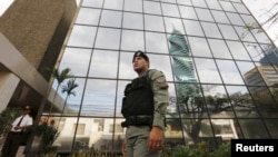 FILE - A police officer stands guard outside the Mossack Fonseca law firm office in Panama City, April 12, 2016.