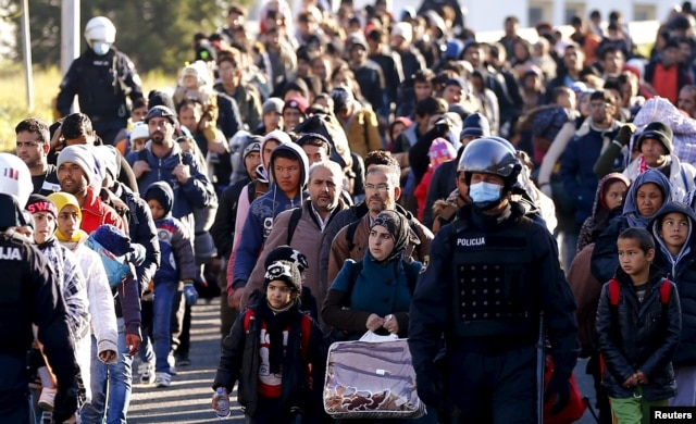 FILE - Slovenian police officers guide migrants towards the Austrian border town of Spielfeld, in the village of Sentilj, Slovenia, Nov. 18, 2015.