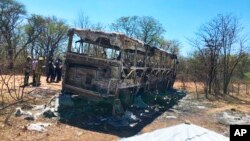 Emergency services stand near to a burned out bus after a bus accident in Gwanda about 550 kilometres south of the capital Harare, Nov. 16, 2018. Police in Zimbabwe say more than 40 people have been killed in a bus accident Thursday night.