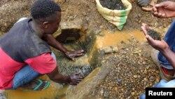 Un mineur nettoie de l'étain avant d'être pesé, et ensuite préparé à être transporté rprès d'une grande ville où le minerai sera exporté à Kalimbi depuis la mine d'étain de Nyabibwe, RDC.