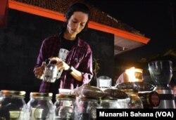 Jihan Fajari, coffee brewer sedang menyajikan kopi, coffee brweing dihadapan pengunjung Festivak Kopi Prawirotaman, Kamis malam (16/7/2017) (foto: VOA/Munarsih Sahana).