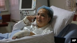FILE - Afghan lawmaker Shukria Barakzai, injured in an attack Nov. 16, talks on her phone from her hospital bed in Kabul, Afghanistan, Nov. 23, 2014.