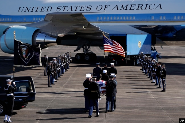 The flag-draped casket of former President George H.W. Bush is carried by a joint services military honor guard to Special Air Mission 41 at Ellington Field during a departure ceremony Monday, Dec. 3, 2018, in Houston, Texas.