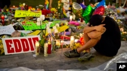 Jean Dasilva sits next to a makeshift memorial for the victims of Sunday's mass shooting at the Pulse Orlando nightclub as he mourns the loss of his friend Javier Jorge-Reyes Tuesday, June 14, 2016.