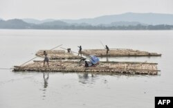 Vendors steer a bamboo pontoon along the Brahmaputra River in Guwahati, India, June 1, 2017.