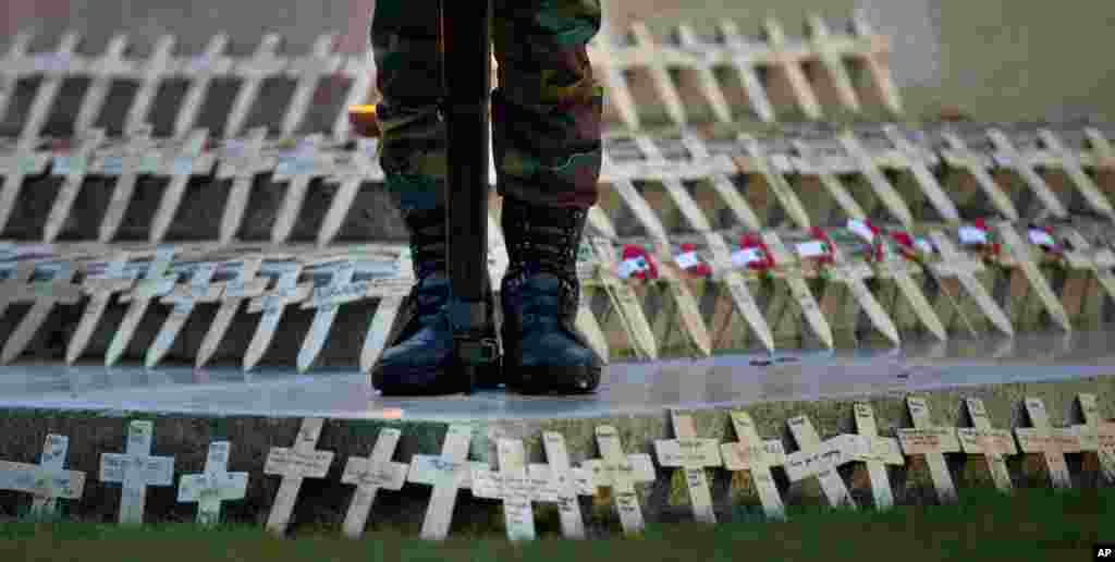 A soldier stands on a memorial filled with wooden crosses and red poppies during an Anzac Day service at Polygon Wood in Zonnebeke, Belgium. Anzac Day is commemorated by New Zealand and Australia to remember the service of those who fought in all wars.