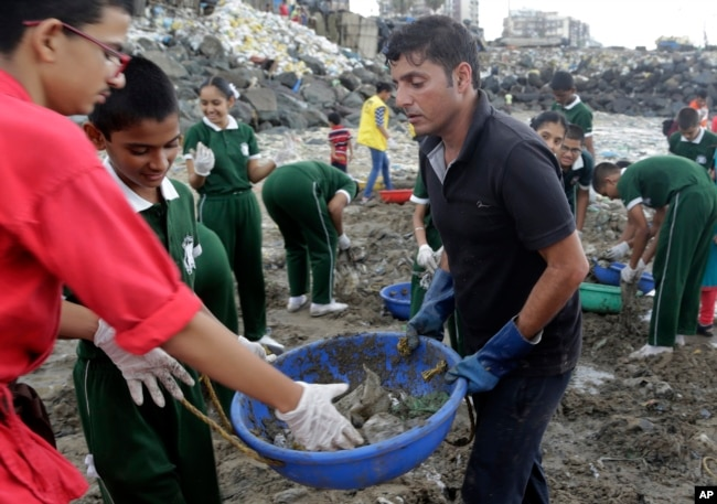 FILE - Afroz Shah, in black, participates in a clean up drive with school children at the Versova beach on the Arabian Sea coast in Mumbai, India.