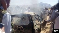 Yemenis gather around a burned car after it was targeted by a drone strike, which killed three suspected al-Qaida militants, between Marib and Chabwa provinces, a desert area east of Sana'a, Jan. 26, 2015.