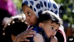 A Syrian refugee carries her sister through a camp set up near the village of Ketermaya in Lebanon in March.