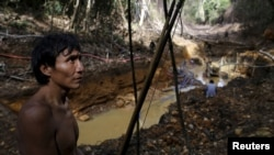 FILE - An Yanomami indian stands near an illegal gold mine during Brazil's environmental agency operation against illegal gold mining on indigenous land, in the heart of the Amazon rainforest, in Roraima state, Brazil, April 17, 2016.
