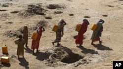 FILE - Women carry jerry cans of water from shallow wells dug in the sand along the Shabelle River bed, which is dry due to drought in Somalia's Shabelle region, March 19, 2016.