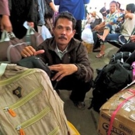 Wahyudi, a food vendor, will have to spend the night at the station with the boxes of clothes he plans to give to his children.