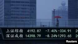 An electronic board, showing the benchmark Shanghai and Shenzhen stock indices, overlooks a pedestrian overpass at the Pudong financial district in Shanghai, China, June 26, 2015.