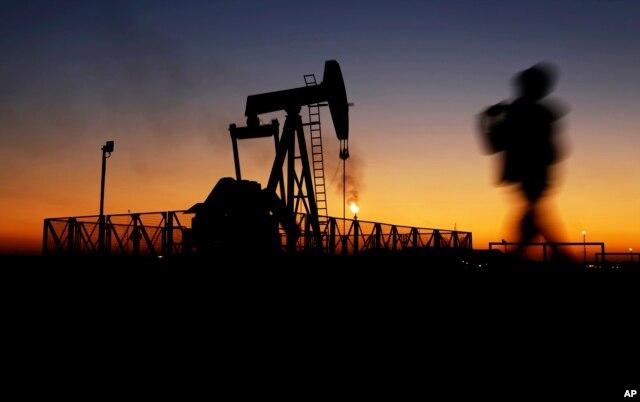 A boy walks by an oil pump at sunset Jan. 18, 2016, in the desert oil fields of Sakhir, Bahrain.