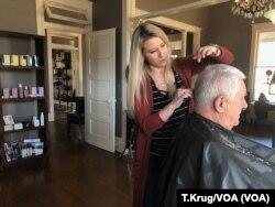미국 워싱턴의 미용사가 고객의 머리카락을 자르고 있다.