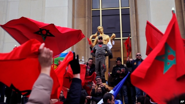 Demonstrators wave Moroccan flags during a protest in Paris, March 20, 2016.