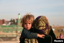 FILE - A woman carries a child as they return with others to the town of Hisha, after the Syrian Democratic Forces (SDF) took control of the area from Islamic State militants, in the northern Raqqa countryside, Syria, Nov. 14, 2016.