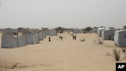 FILE - Nigerians who fled Boko Haram to Chad walk through the Baga Solo refugee camp in Chad, March 4, 2015.
