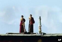 两位年青西藏僧侣在吹长角号