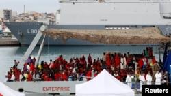 Des migrants attendent pour descendre du bateau de la Royal Navy Ship HMS Enterprise dans un port sicilien, à Catane, Italie, le 23 octobre 2016.