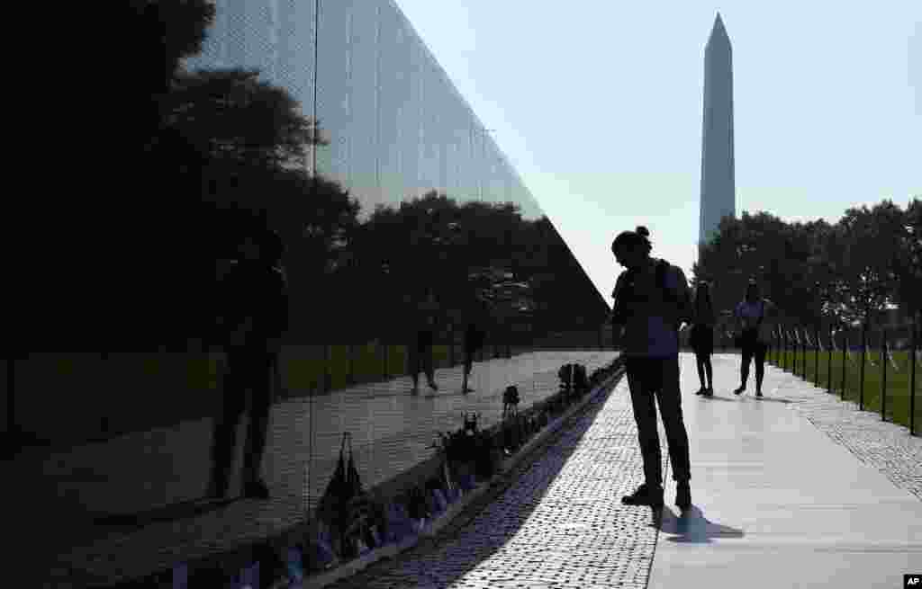 With the Washington Monument in the background, people visit the Vietnam Memorial in Washington on the start of the Memorial Day weekend.