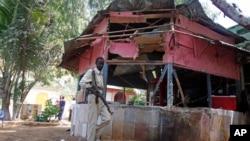 索馬里首都摩加迪沙一家餐館發生自殺炸彈襲擊,一名士兵走近現場。
